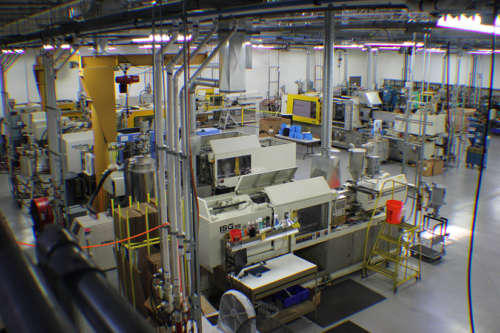 A photo of several injection molding machines on a shop floor